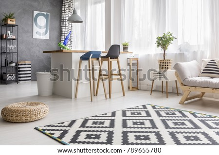 Open space living room interior with geometric carpet and dining area with barstools and white bin #789655780