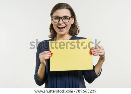 Smiling middle aged woman with yellow sheet of paper on white background #789665239