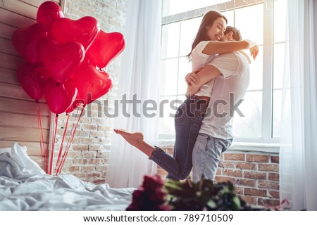 Beautiful young couple at home. Hugging, kissing and enjoying spending time together while celebrating Saint Valentine's Day with red roses on bed and air balloons in shape of heart on the background. #789710509