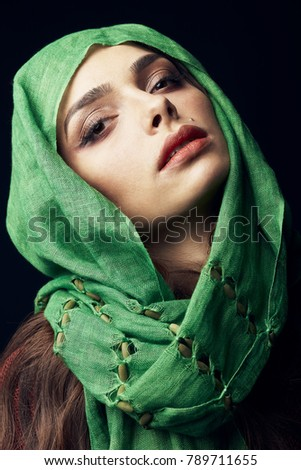 Close-up studio portrait of attractive east woman with beautiful dark eyes, big lips and birthmark near lips, wearing green hijab.  #789711655