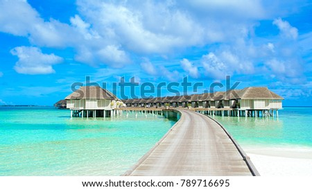 South Ari Atoll, Maldives - 12 July 2017: Beautiful tropical landscape with wooden villas of luxury resort above the crystal turquoise water of the Indian Ocean, Maldives island, 12 July 2017 #789716695