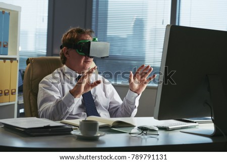 Businessman in VR goggles working at his table in office #789791131