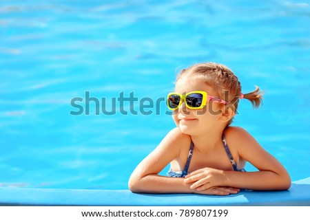 Smiling cute little girl in sunglasses in pool in sunny day. Royalty-Free Stock Photo #789807199