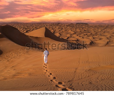 Young man in casual clothes walking in the Dubai desert during sunset #789817645