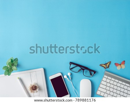 top view office desk workspace with smartphone, notebook, graphic tablet, keyboard, glasses and mouse on blue background with copy space, graphic designer, Creative Designer concept