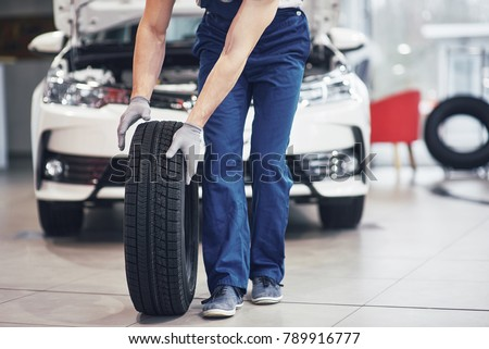 Mechanic holding a tire tire at the repair garage. replacement of winter and summer tires. #789916777