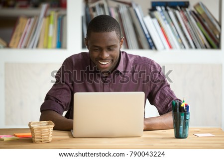 Smiling african-american man using laptop sitting at home office desk, happy excited black e business owner looking at computer screen pleased by reading good news, chatting in social network #790043224