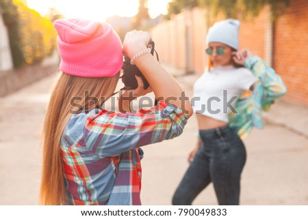 The girl is taking pictures of another girl at sunset