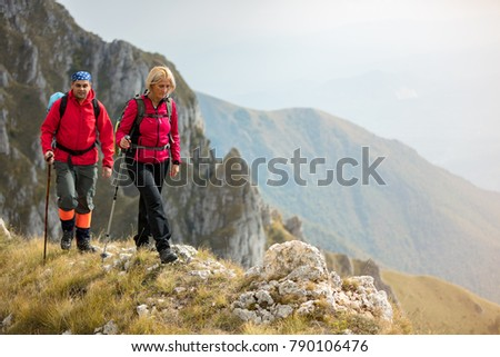 adventure, travel, tourism, hike and people concept - smiling couple walking with backpacks outdoors #790106476
