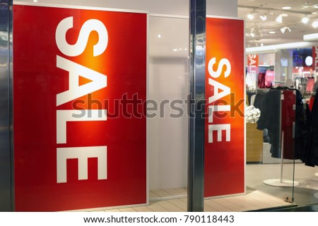 A sign of the sale against the backdrop of the store. Sale sign in the clothing shop.