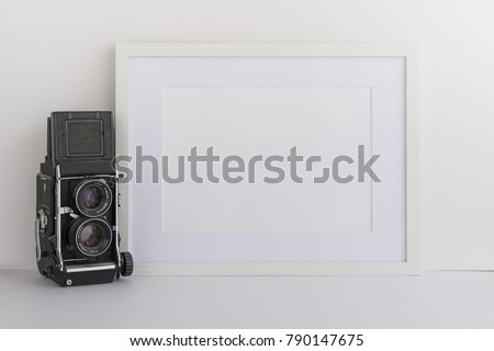 A4 A3 A5 white wooden picture frame with white blank space for your quote, logo or work or for overlay standing next to vintage camera. Blank space for bloggers, marketers or website designers.