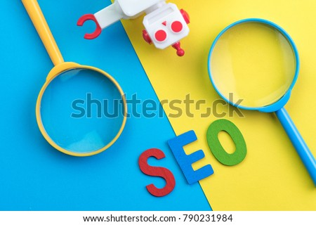 SEO Search engine optimization concept with blue and yellow magnifying glass, alphabet abbreviation SEO and robot on colorful background. #790231984