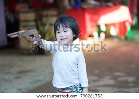 The asian baby girl playing a wood gun.She very happy and fun. Royalty-Free Stock Photo #790261753