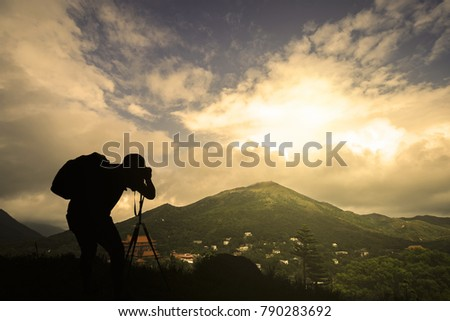 Silhouette of a traveler taking photo sunset in the mountains #790283692