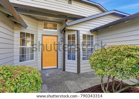 Entrance porch with taupe exterior paint, yellow front door and large windows. #790343314