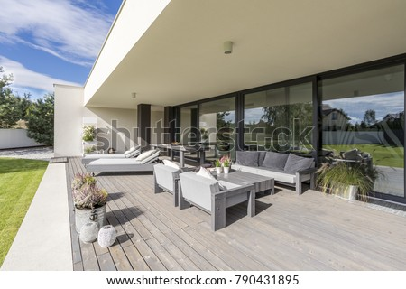 Grey garden furniture on board floor with flowers in pots on terrace of spacious mansion #790431895