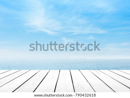 The blur cool sea background with wood floor foreground on horizon tropical sandy beach; relaxing outdoors vacation with heavenly mind view at a resort deck touching sunshine, sky surf summer clouds. #790432618