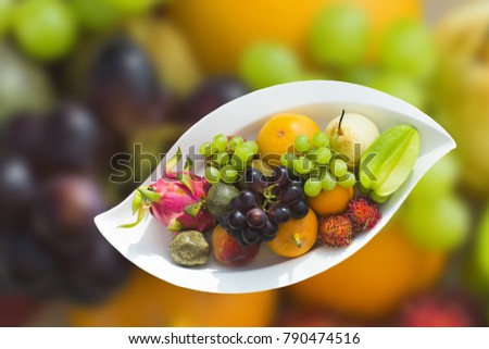 Tropical fruits on a white plate. The object is isolated. The background is similar, blurred. #790474516