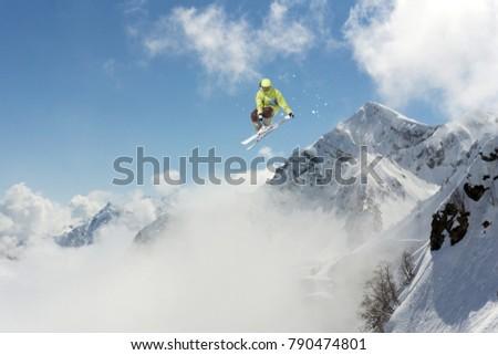 Skier jump in the mountains. Extreme ski sport. Freeride. #790474801