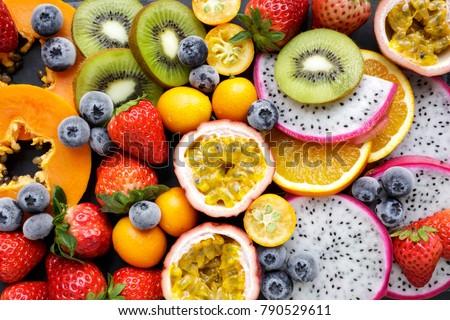 Fresh fruits on a black background. Exotic fresh fruits on a blackboard. Strawberry, blueberry, papaya, dragon fruit, kiwi, passion fruit. Royalty-Free Stock Photo #790529611
