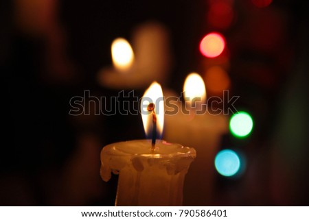 The candles and the flames closeup on dark background with colored lights #790586401