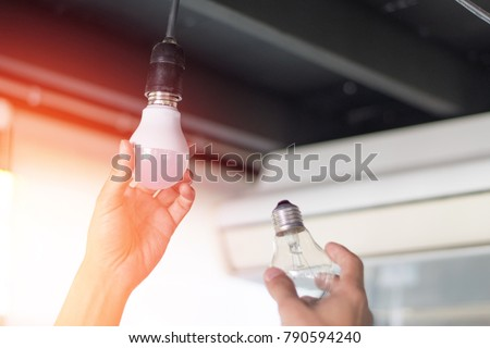 Power saving concept. Asia man changing compact-fluorescent (CFL) bulbs with new LED light bulb.  #790594240