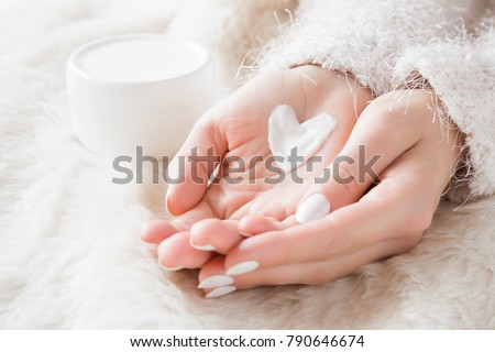Beautiful groomed woman's hands with cream jar on the fluffy blanket. Moisturizing cream for clean and soft skin in winter time. Heart shape created from cream. Love a body. Healthcare concept.  #790646674