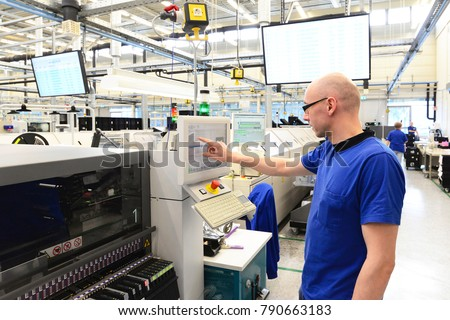 production and assembly of microelectronics in a hi-tech factory - man operates machine in production  #790663183