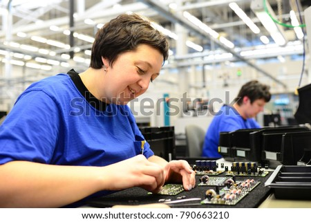 production and assembly of microelectronics in a hi-tech factory - older woman assembles components  #790663210
