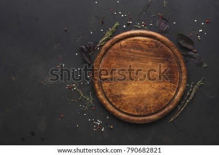 Round wooden plate with herbs and salt on dark wooden background top view Royalty-Free Stock Photo #790682821