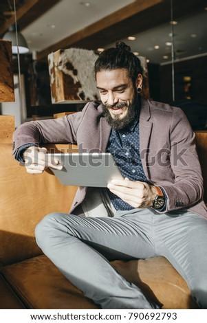 Modern elegant Caucasian businessman reading on tablet  and smiling. #790692793