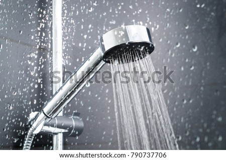 Fresh shower behind wet glass window with water drops splashing. Water running from shower head and faucet in modern bathroom. Royalty-Free Stock Photo #790737706