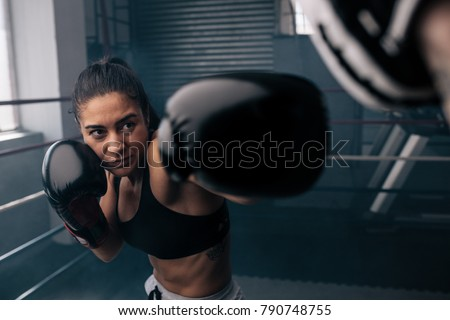 Boxer practicing her punches at a boxing studio. Close up of a female boxer punching inside a boxing ring. #790748755