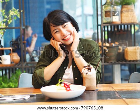 Young Asian woman take a photo by smart phone and joyful with delicious pancake and dessert in coffee shop. #790765108