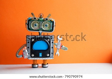 Robot handyman with hand wrench light bulb. Fixing maintenance concept. Creative design mechanic toy character. Orange wall, light floor background. Copy space. #790790974