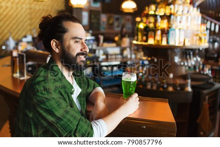 people, leisure and st patricks day concept - happy man drinking green beer at bar or pub #790857796