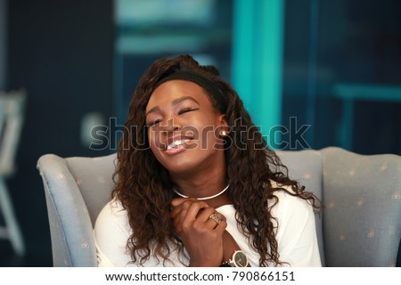 Satisfied African-American woman sitting in armchair and making wish while keeping eyes closed and arms clasped.  #790866151