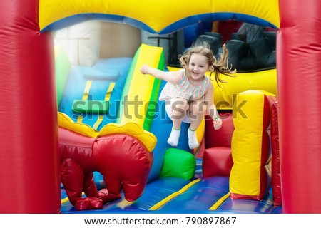 Child jumping on colorful playground trampoline. Kids jump in inflatable bounce castle on kindergarten birthday party Activity and play center for young child. Little girl playing outdoors in summer. #790897867