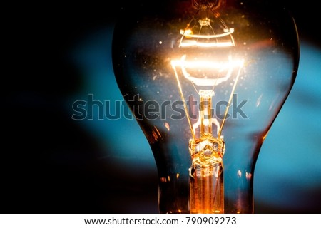 Standard Incandescent Light Bulb on Black Background #790909273