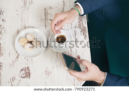 Top view of young  man using mobile phone sitting by cafe table drinking coffee and eating cookies #790923271