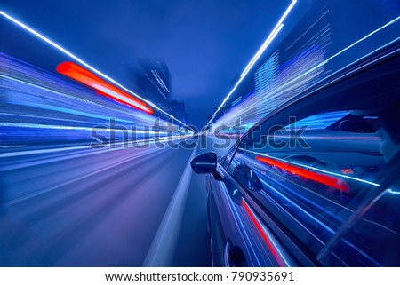 View from Side of Car moving in a night city, Blured road with lights with car on high speed. Concept rapid rhythm of a modern city. #790935691