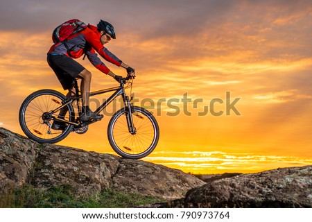 Cyclist in Red Riding the Bike on the Autumn Rocky Trail at Sunset. Extreme Sport and Enduro Biking Concept. #790973764