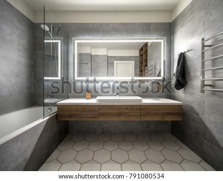 Bathroom in a modern style with gray and white tiles. There is a large mirror with luminous lamps, tabletop with wooden drawers and sink, bath with shower and glass partition, towel rack and a hanger. #791080534