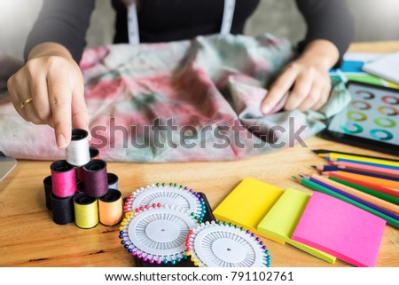Beautiful young fashion designer woman choosing thread for sewing clothes with sewing machine #791102761