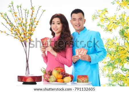 Smiling young couple in traditional dresses holding lucky money envelopes #791132605