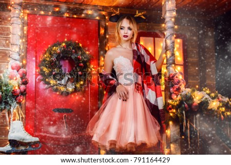 Happy girl in a beautiful dress, wrapped in a blanket, stands near the house decorated for Christmas. Time for miracles. Merry Christmas and Happy New Year. #791164429