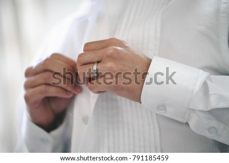 A man wearing white shirt. buttoning shirt. Groom #791185459