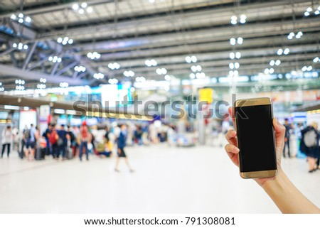 Hand holding mobile phone with airport terminal blurred crowd of Travelling people on the background, Bokeh light, Social network, internet,Traveling concept #791308081