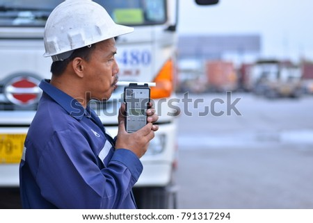 BANGKOK,THAILAND:January 11,2018:The driver is blowing the air in the monitor,whether it was drinking or not. before driving the truck. #791317294