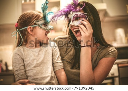 Mother and daughter have play with carnival mask.  #791392045